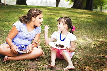 Girl feeding sister cake at birthday party in park