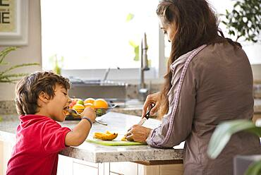 Hispanic mother and son eating fruit in kitchen
