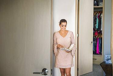 Hispanic woman holding journal in closet