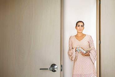 Worried Hispanic woman peering through door crack