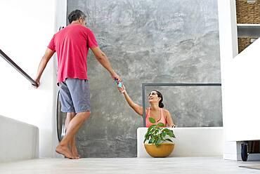 Hispanic woman reaching for boyfriend in modern living room
