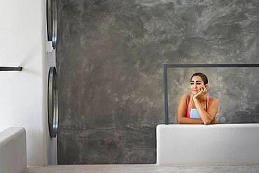 Hispanic woman sitting in modern living room