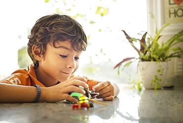 Hispanic boy playing with toy cars on counter