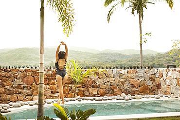 Hispanic woman stretching by swimming pool