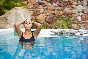 Hispanic woman swimming in pool