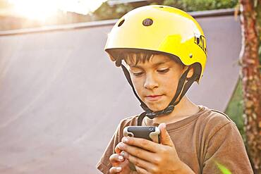 Mixed race boy in helmet using cell phone