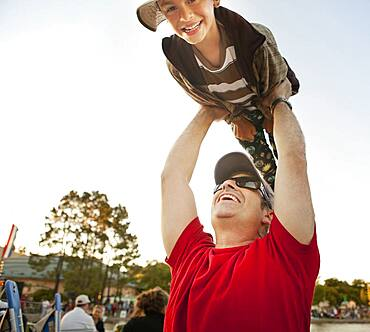 Father lifting son under blue sky