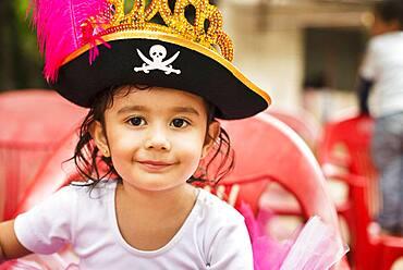 Hispanic girl wearing pirate hat at party