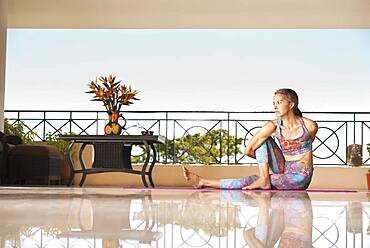 Hispanic woman practicing yoga on balcony