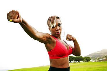Black woman boxing in field