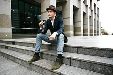 Caucasian businessman drinking coffee on steps