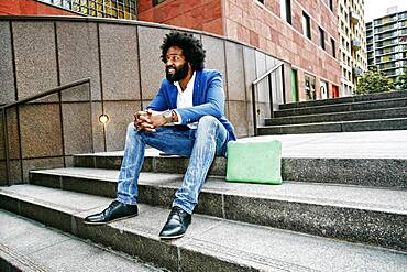 Mixed race businessman sitting on steps