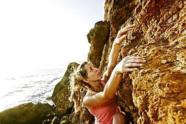 Woman climbing rock formation