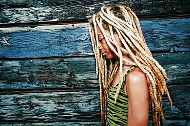 Black woman with dreadlocks at wooden wall