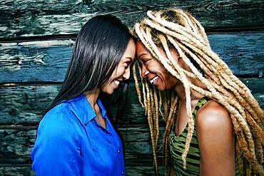 Smiling women touching foreheads at wooden wall
