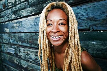 Black woman smiling at wooden wall