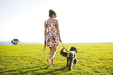 Caucasian woman walking dog in field