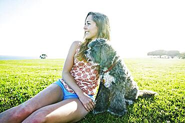 Caucasian woman sitting in field with dog