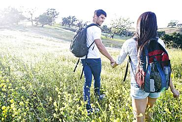 Couple carrying backpacks in field