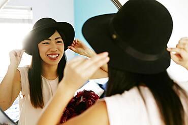 Japanese woman adjusting hat in mirror