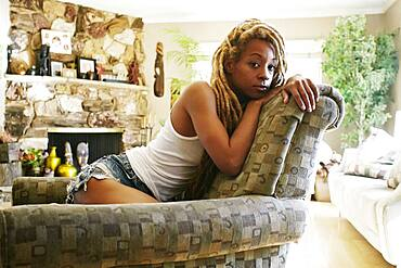 Black woman sitting on armchair in living room