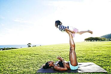 Mother holding daughter with legs in park