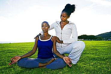 Woman practicing yoga with teacher in park
