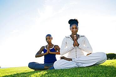 Women meditating in park