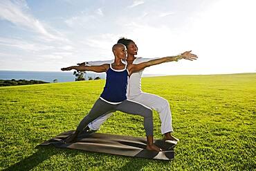 Women practicing yoga in park