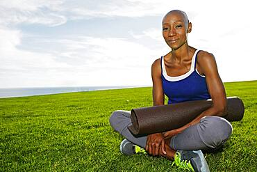 African American woman holding yoga mat in park