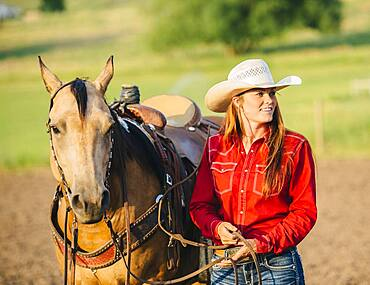 Caucasian cowgirl walking horse on ranch
