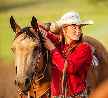 Caucasian cowgirl standing with horse on ranch