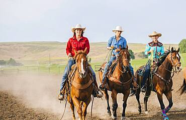 Cowgirls riding horses on ranch