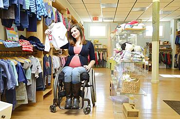 Pregnant paraplegic woman in wheelchair shopping in baby store
