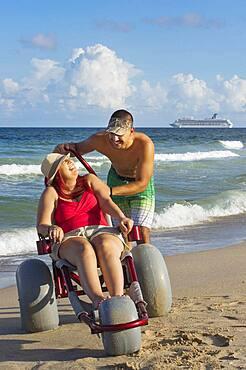 Man pushing paraplegic girlfriend in wheelchair on beach