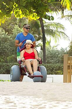 Man pushing paraplegic girlfriend in wheelchair