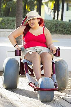 Paraplegic woman in wheelchair on walkway