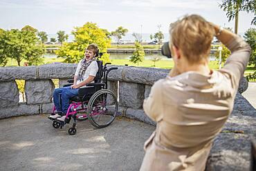 Mother photographing paraplegic daughter