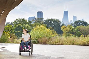 Paraplegic woman sitting in wheelchair under city skyline