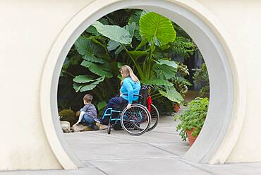 Paraplegic mother and son admiring plants