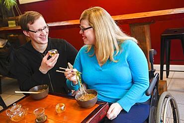 Paraplegic woman and boyfriend eating noodles in tea shop