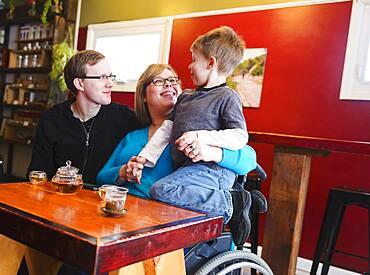 Paraplegic mother holding son in tea shop