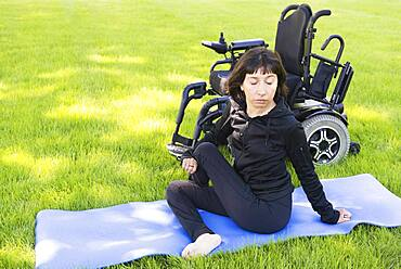 Disabled woman stretching legs in park