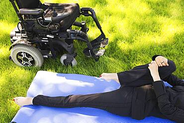 High angle view of disabled woman stretching legs in park