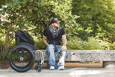 Disabled man and wheelchair sitting on stone bench