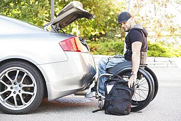 Disabled man in wheelchair packing car trunk