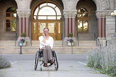 Disabled woman sitting in wheelchair outside courthouse