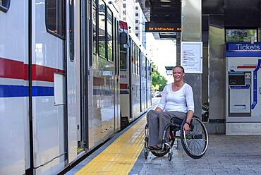 Disabled woman in wheelchair waiting in train station