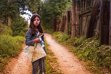 Caucasian teenage girl carrying kite on dirt road