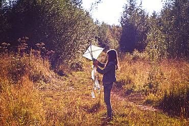 Caucasian teenage girl holding kite in field